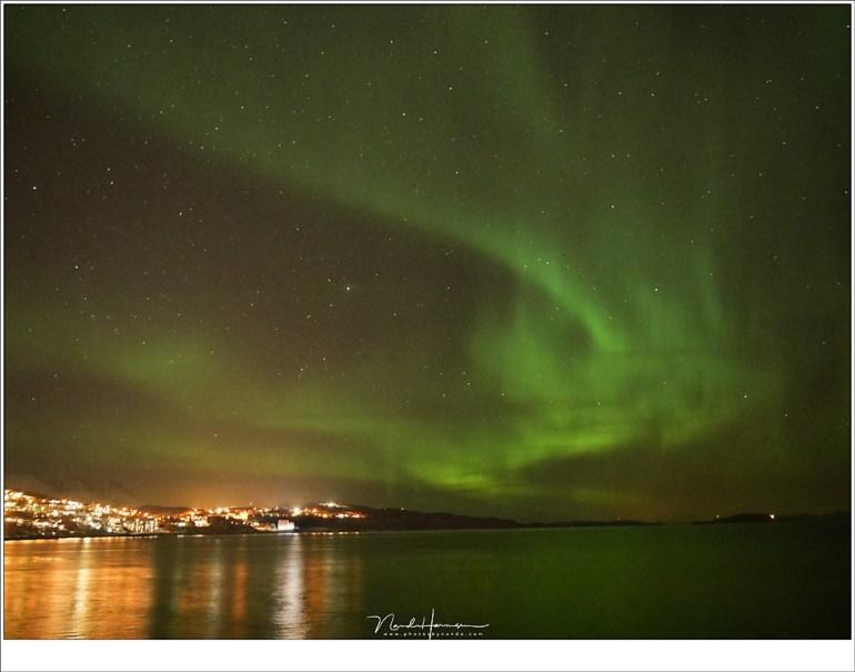Noorderlicht boven de haven van Harstad, gefotografeerd zonder statief, met de camera op een gladde rots.