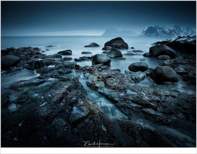 Het strand van Myland met een ogenschijnlijke rustige, vlakke zee. In de verte doemen de bergtoppen bij Uttakleiv en Haukland op. (24mm | ISO100 | f/16 | 240sec met 10 stops ND)