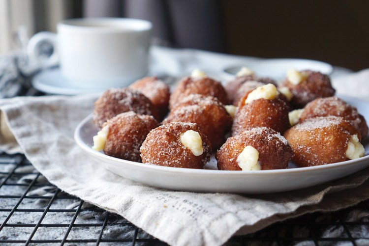 Gluten free churro donut holes rolled in cinnamon sugar and filled with hazelnut flavoured pastry cream
