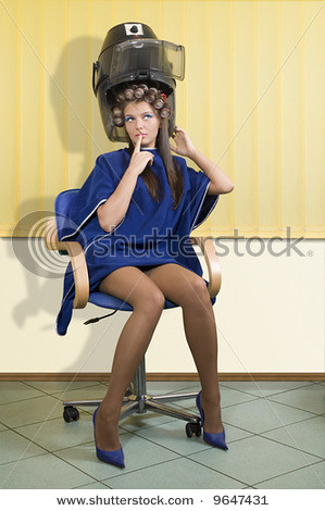 Stock Photo Young Woman Sitting Under A Hairdryer With Rol