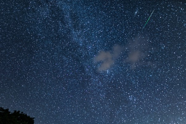 A Persied Meteor and a cloud in front of a portion of the Milky Way and the Andromeda Galaxy