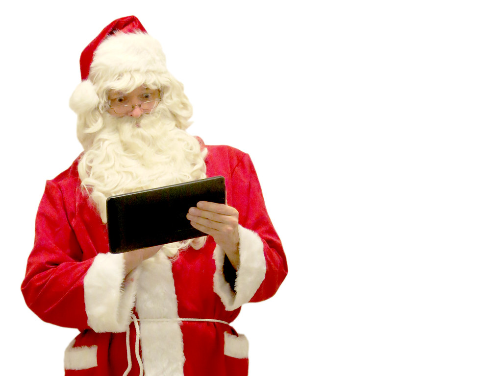 Santa Claus Tapping A Tablet Ideal For An E Card Or