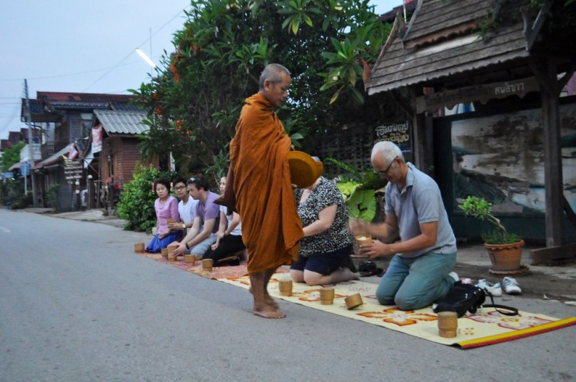Visitors give sticky rice offerings to a monk in Chiang Khan, Thailand, March 2015.