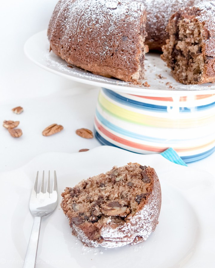 chocolate chip bundt cake with pecans, sliced on a cake with whole cake in background