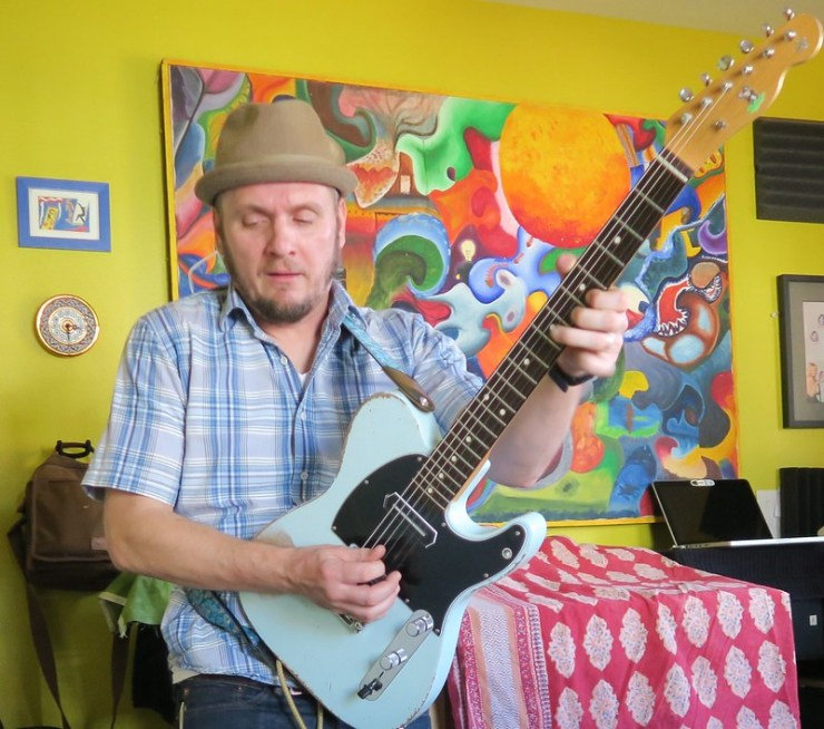 Gray and his blue Telecaster on a sea of color