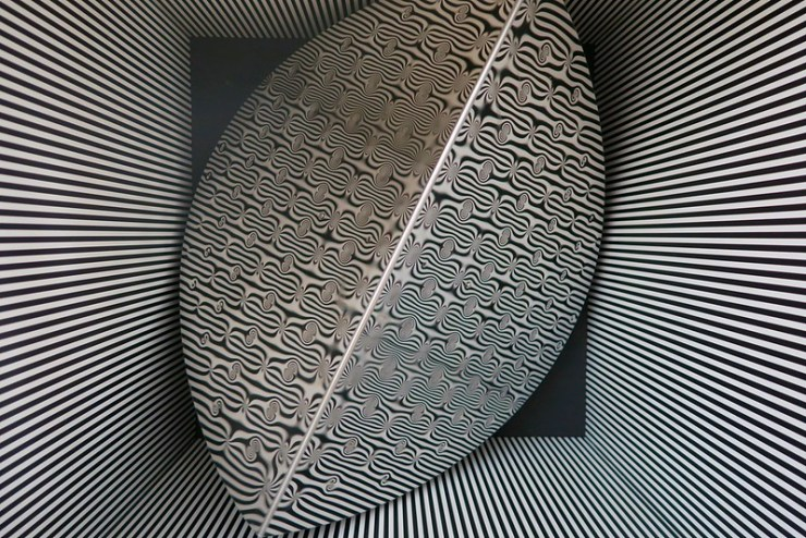 shiny spinning metal shape with divets in a black and white lined box