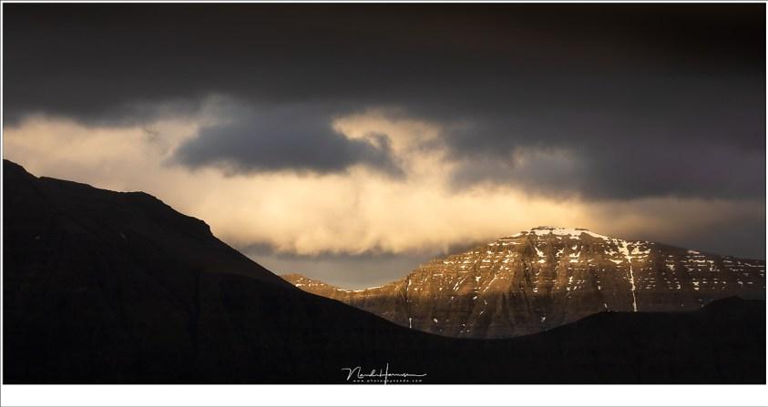 Over de schouder van de bergen van Kalsoy worden de toppen van het eiland Kunoy door de ondergaande zon verlicht. Een prachtig uitzicht vanaf het dorp Gjógv.
