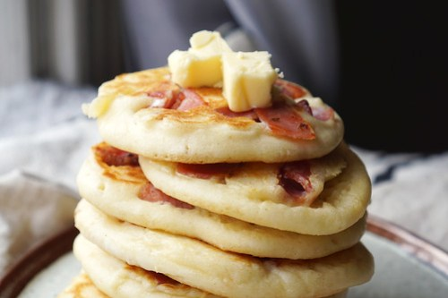 Gluten free American style bacon pancakes with melted butter on top.