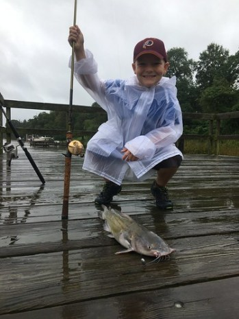Photo of Boy with a channel catfish on a rainy day.