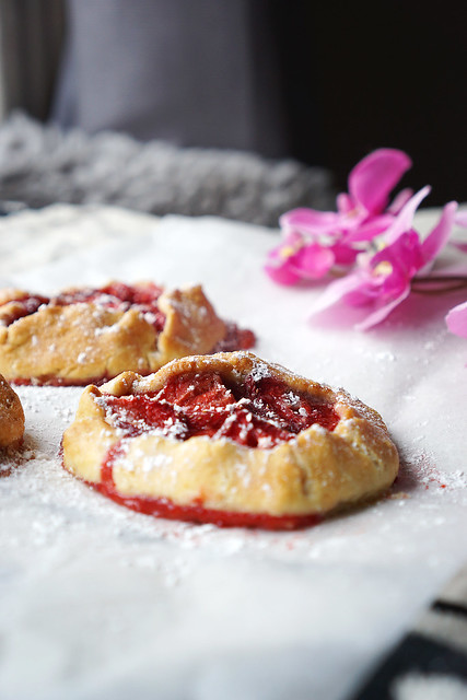 Mini gluten free strawberry rustic pies with a sprinkle of icing sugar.