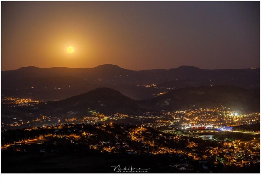 De Volle Maan komt op boven de stad Le-Puy-en-Velay; een waanzinnig uitzicht van hoog boven de verlichte stad.