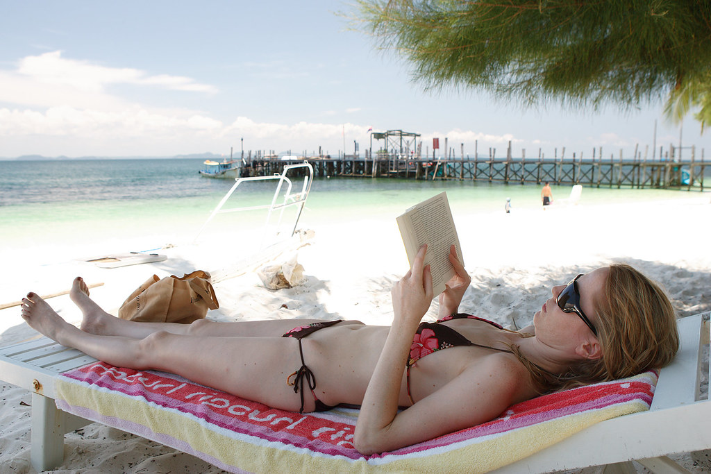 Girl reading book on beach chair Rawa Island Malaysia