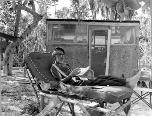 Old hermit Roy Ozmer reading a letter on a selfmade loung