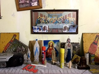 painting of last supper and various saints icons on a wall in a house in palmarin, senegal