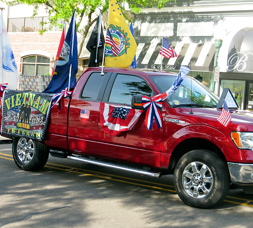 red truck decorated with Vietnam War veteran flag, American flag, and other flags