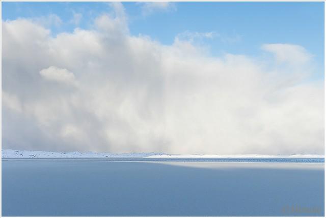 Het licht speelt een spel met het met sneeuw bedekte ijs op het water.