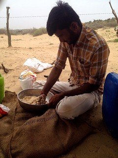an indian man preparing dough for chapati in thar desert