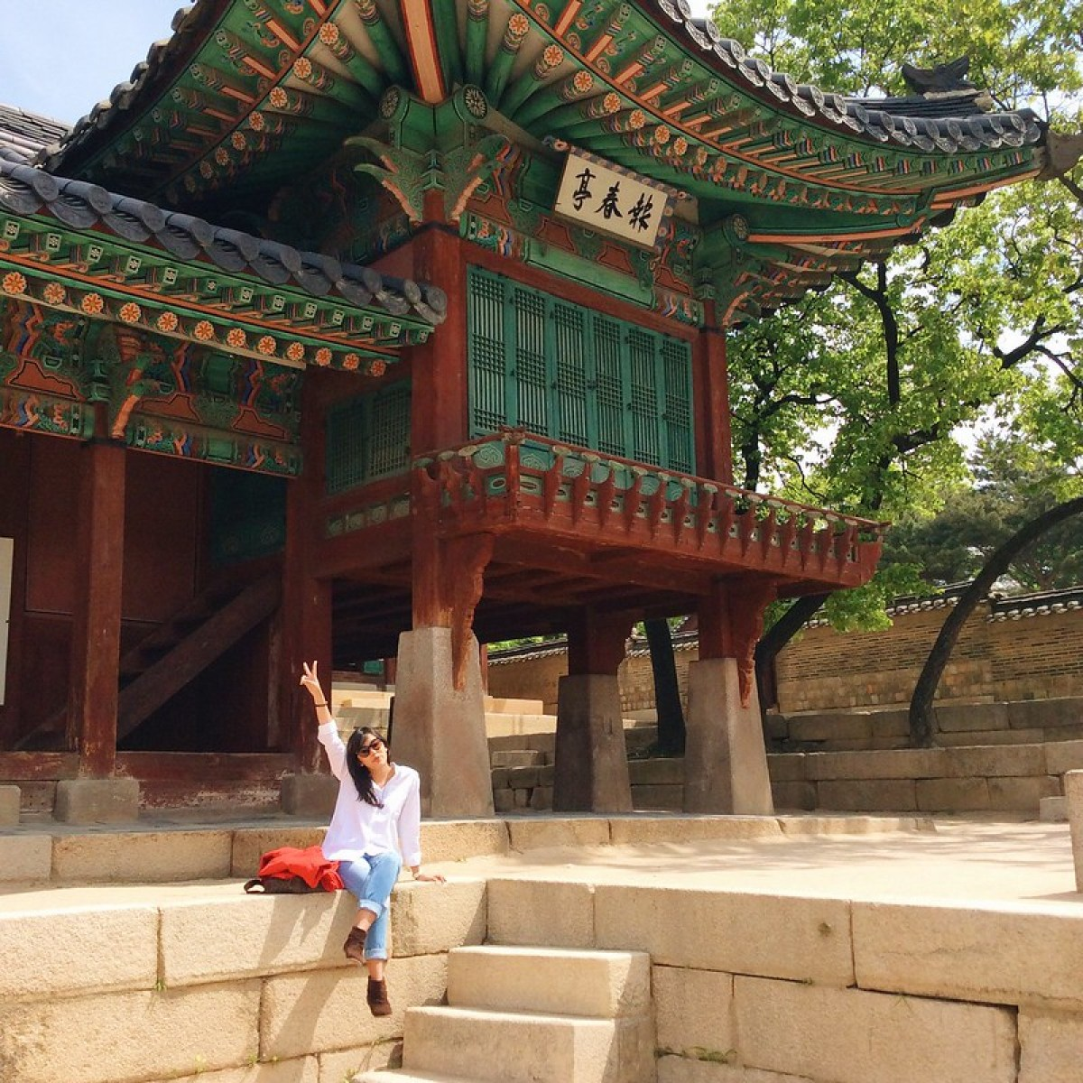 A girl in peace sign in front of a hall in Changdeokgung Palace