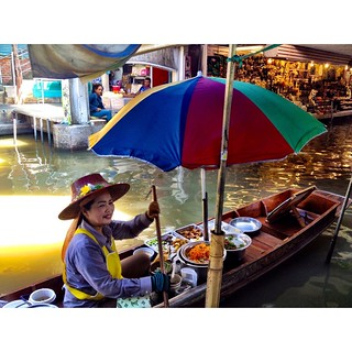 thai woman with colorful parasol making food on a boat in damnoen saduak floating market