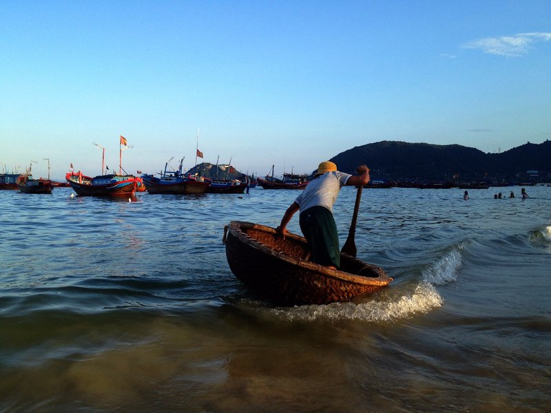 vietnamese man in a basket-like round boat in dai lanh