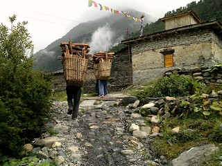 men in nepali village carrying big baskets