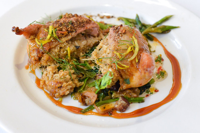 Chicory Coffee Lacquered Quail fire roasted chili and cochon de lait boudin over smoky bacon wilted greens with tabasco pepper jelly and espresso pecan crust