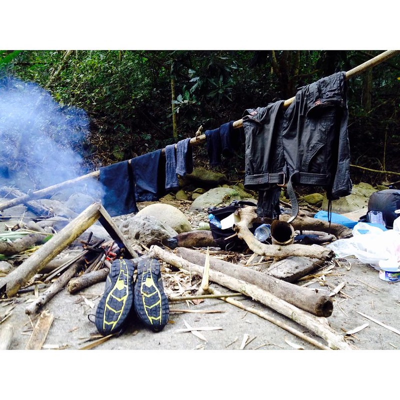 drying clothes and shoes by fire while camping in the jungle