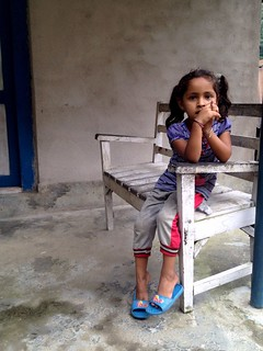little nepali girl sitting on bench in village in annapurna