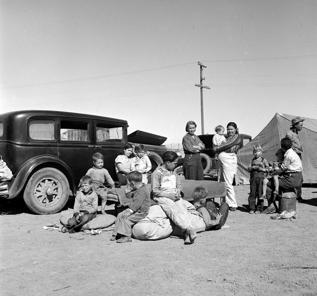 Four families, three of them related with fifteen children, from the Dust Bowl in Texas in an overnight roadside camp near Calipatria, California. March 1937; photo by Dorothea Lange; Library of Congress image.