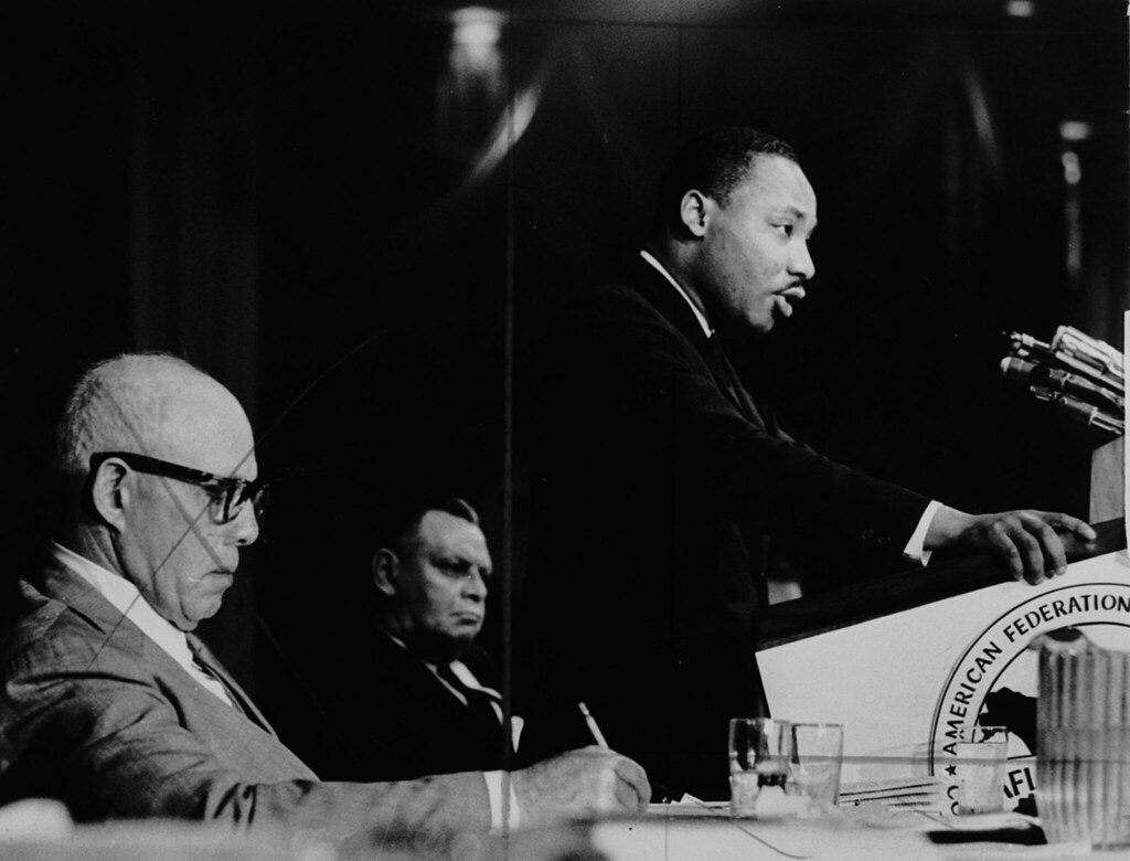 Martin Luther King Jr giving a speech while George Mea