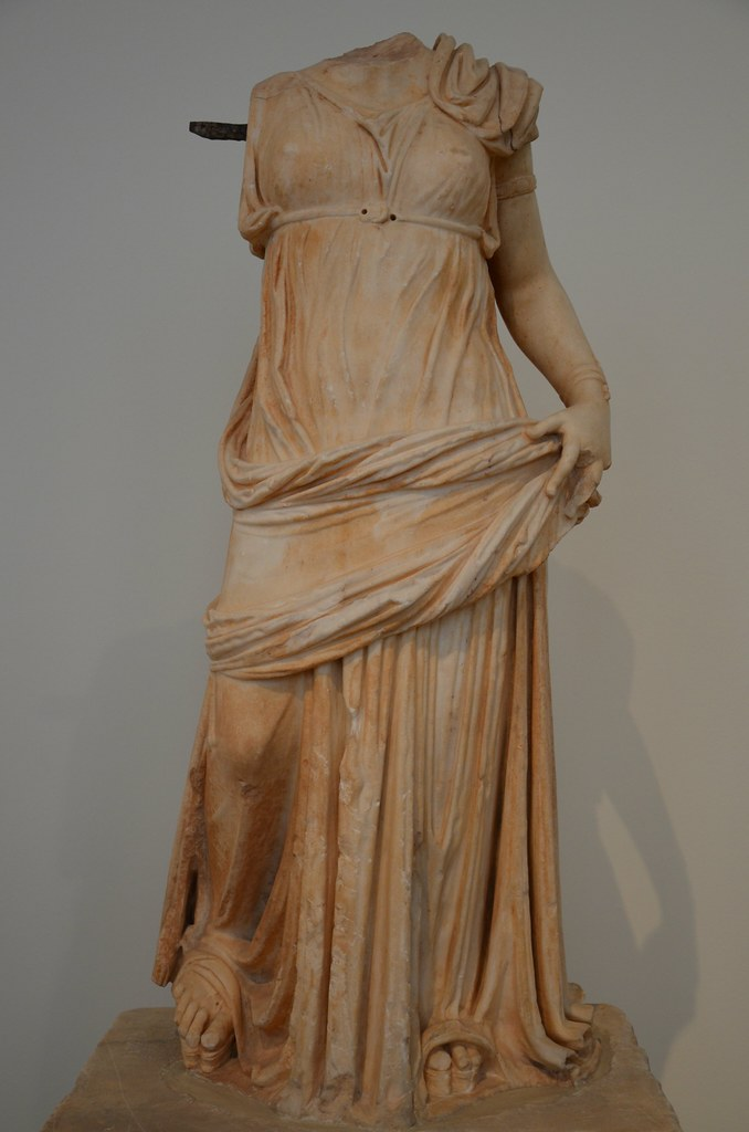 Statue of a woman wearing a transparent chiton girt high