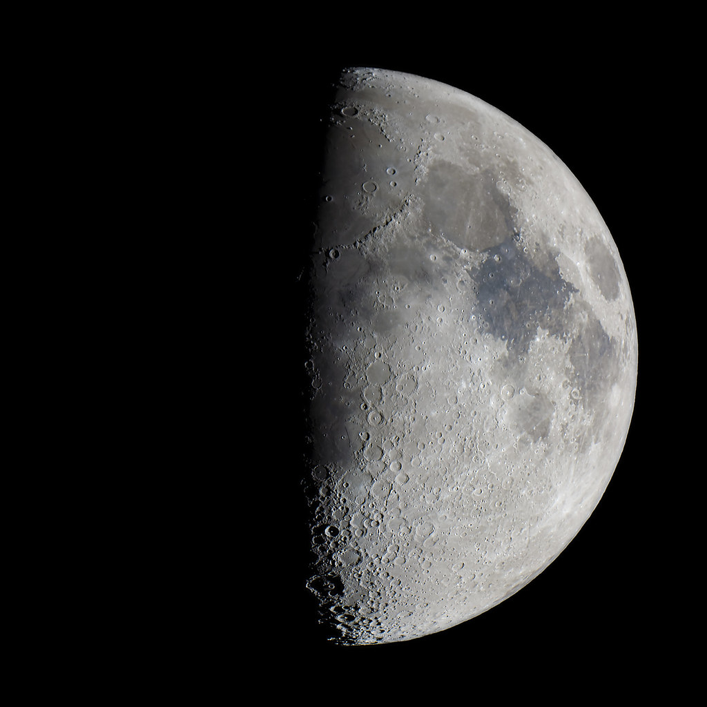A first quarter moon is seen in the sky