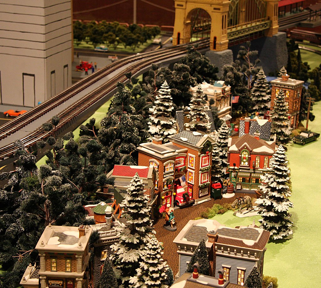 A Miniature Christmas Village And Train Tracks By The Arch