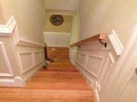 Shadow box wainscoting on both sides of staircase.