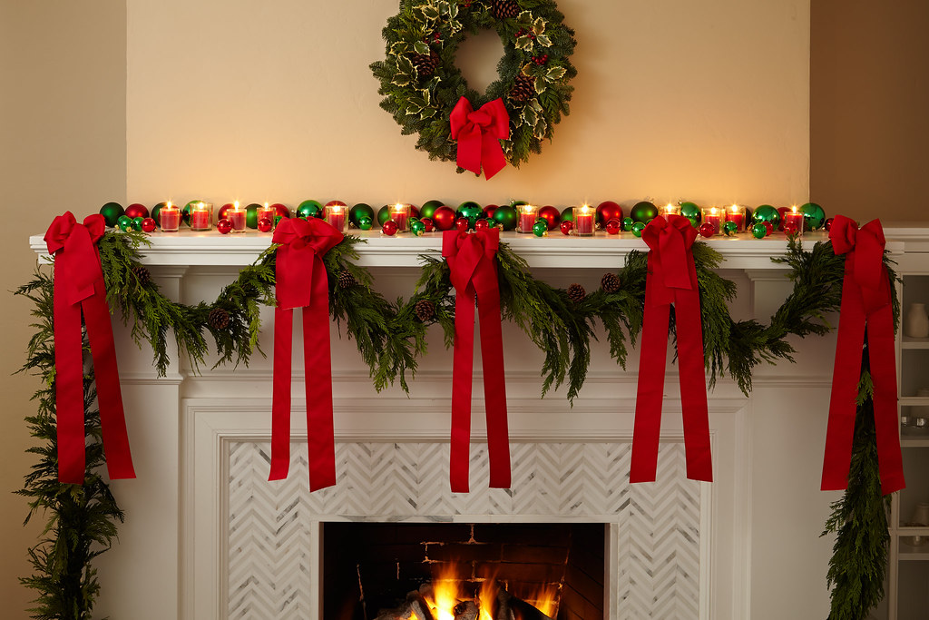 A garland strung across a fireplace mantel with bright red
