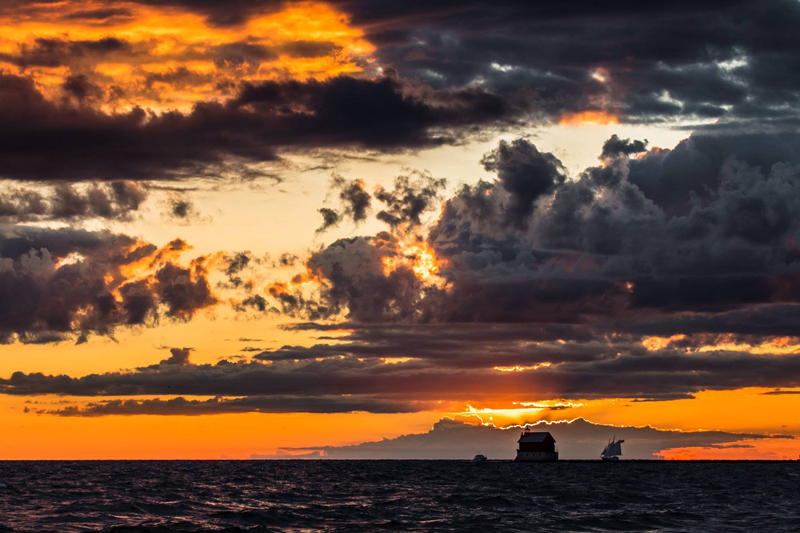 photograph of the grand haven pier with sun setting and clouds