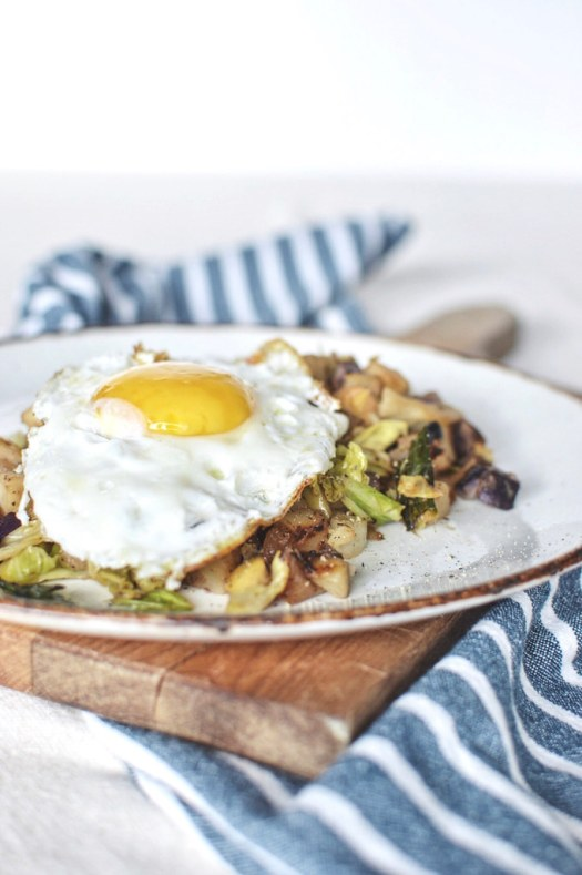 Potato onion apple cabbage has topped with a fried egg
