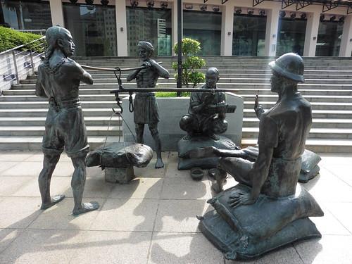 Estatua urbana A Great Emporium (2002) de Malcolm Koh, situada cerca de Asian Civilisation Museum, en Singapur.