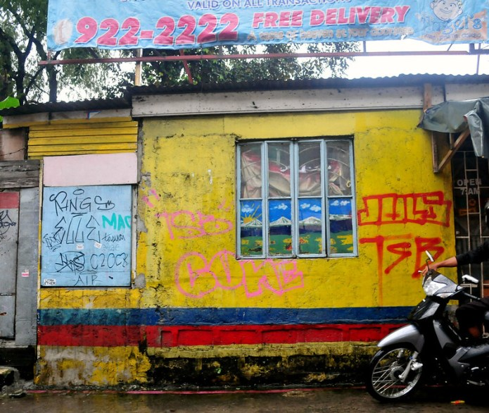 yellow house facade with graffiti and blue and red stripes