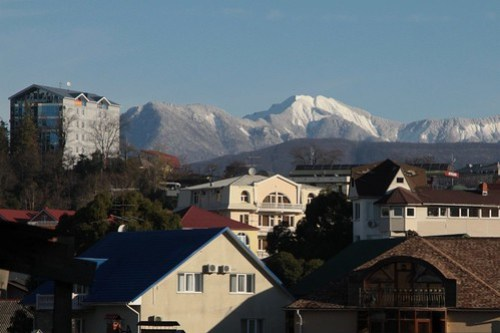 Snow covered mountains tower over the Russian city of Sochi