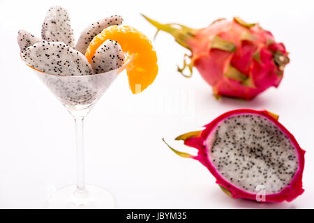The juicy pulp of the Pitahaya blanca presented in a glass and decorated with a mandarine slice. This exotic fruit - Stock Photo