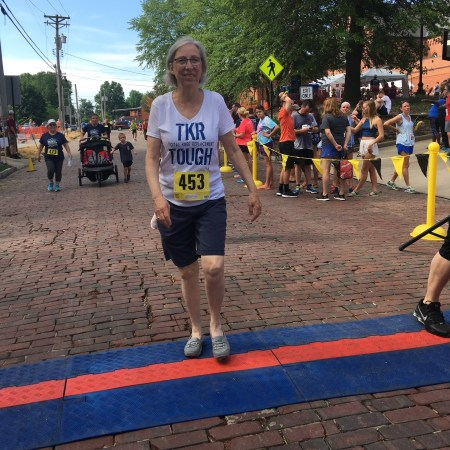 Cheri, a CAO total knee replacement patient, crosses the finish line.