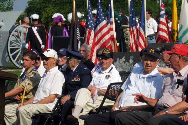 veterans sitting at Veterans Memorial Park, with flags behind them