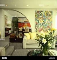 Large abstract painting on wall above pale gray sofa ...