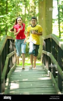 Two Teenagers Running Barefoot Wooden Bridge In