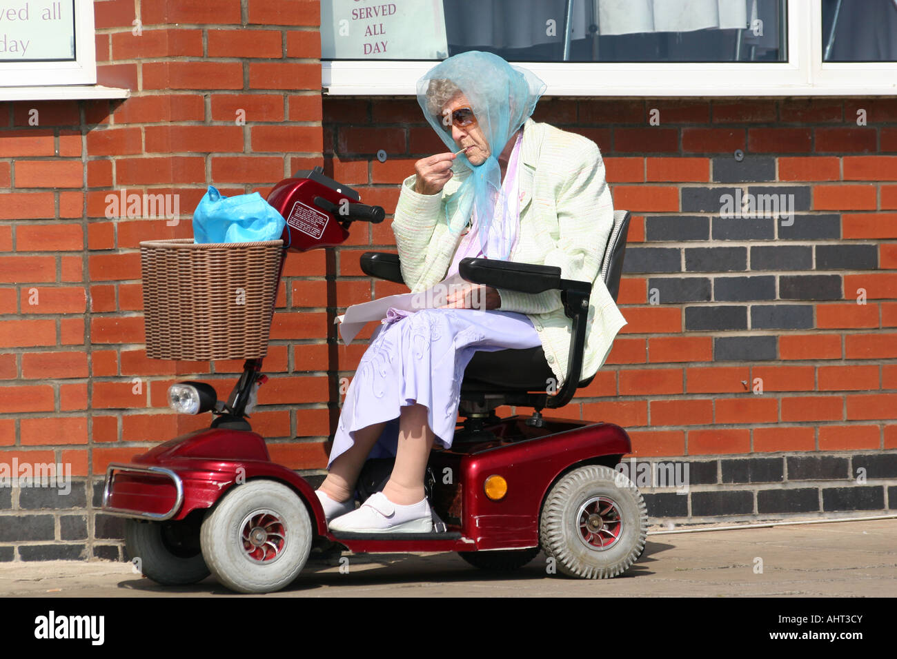 old lady chair pale pink on motorised buggy or wheel eating fish and
