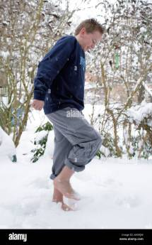 Young Boy Walking Barefoot In Snow Stock Royalty