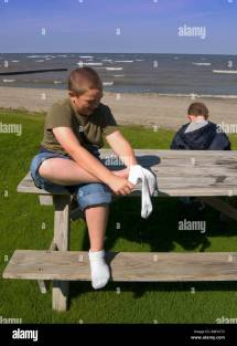 Young Barefoot Boy Puts Socks Wading Lake Erie