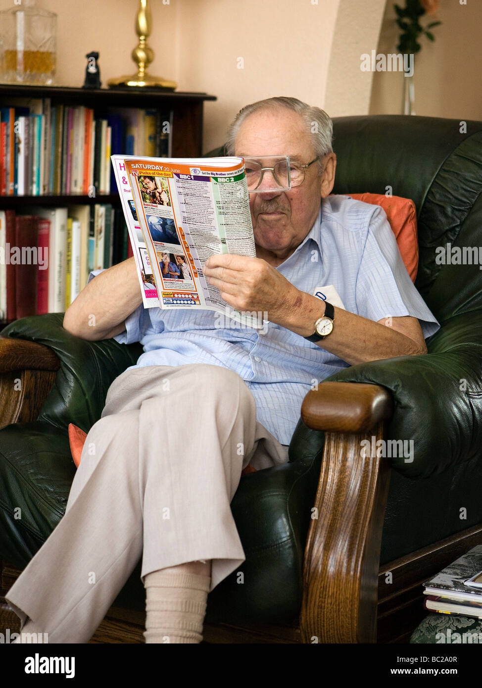 lounge chair leather fritz folding chairs old man sits in his favourite armchair reading the television pages stock photo, royalty free ...