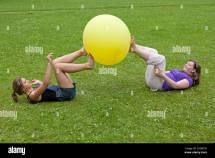 Two Young Girls Balancing Big Balloon Feet